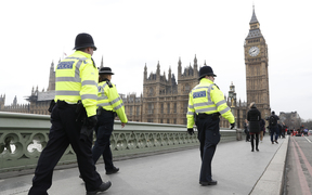 Police patrol across Westminster Bridge toward the Houses of Parliament a day after the attack.
