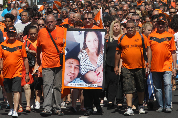 French RCN (racing club de Narbonne) supporters hold a picture of All Black's Jerry Collins and his partner.