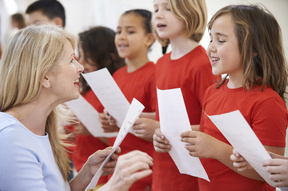 A music teacher helps a group of primary school children singing in a choir (file photo)