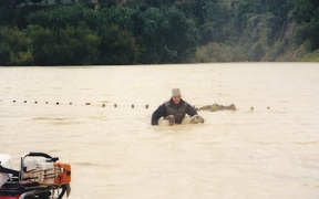 Mike Cranstone rescues sheep on his flooded farm in 2004.