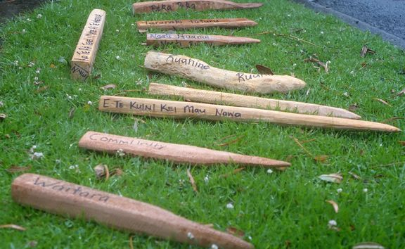 rough wooden pegs lie on the grass