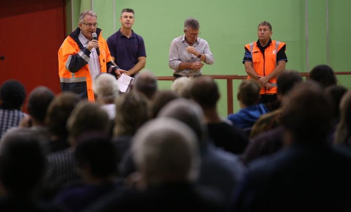 Whakatāne District mayor Tony Bonne speaks at a public meeting of about 500 people after the flooding at Edgecumbe.