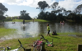 Children play in a newly-formed pool at a Waihi Beach park.