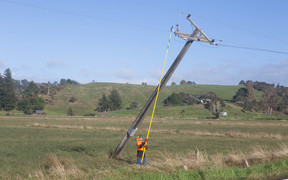 Lines workers right power poles on Wainui Road in Cheddar Valley.
