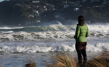 A passer-by watches high waves roll in during a storm surge at Lyall Bay on Wellington's South Coast.