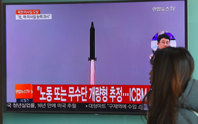 A woman walks past a television screen showing file footage of North Korea's missile launch at a railway station in Seoul on February 12, 2017.