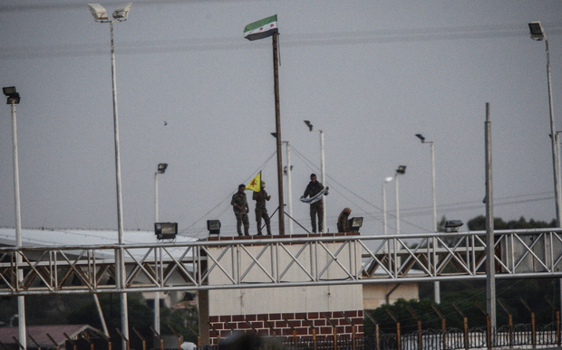 YPG fighters hold their movement's flag.