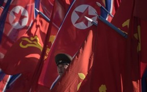 A Korean People's Army (KPA) soldier stands between flags in Pyongyang