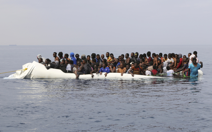 A file photo shows people waiting to be rescued from a sinking dinghy off the Libyan coastal town of Zawiyah, east of the capital, on 20 March, 2017, as they attempted to cross from the Mediterranean to Europe.