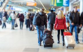 People with suitcases at airport (stock photo).