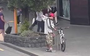 A man uses bolt cutters to snip through a bicycle lock while surrounded by shoppers in Newmarket, Auckland