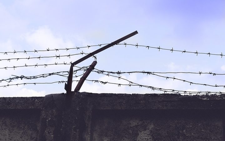 Barbed wire running along top of high wall