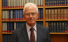Sir Michael Cullen poses in the Labour Caucus Room in front of a bookcase of Hansard's verbatim reports of Parliament.