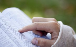 A file photos shows a woman's hand pointing to a Bible passage.