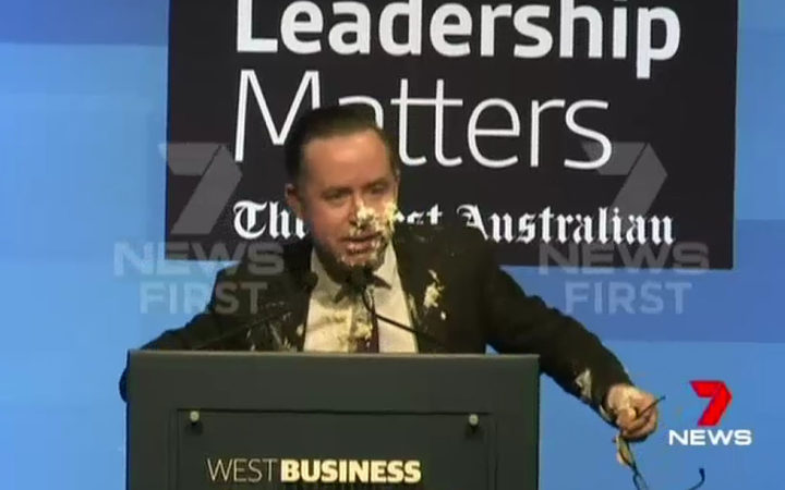 A screenshot from 7 News footage shows Qantas chief executive Alan Joyce with his face covered with pie.