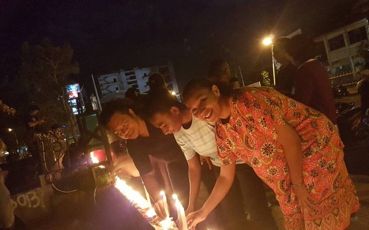 People in Jayapura light candles to show support for the jailed former governor of Jakarta, Ahok.
