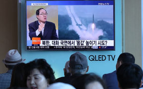 People watch a television news programme, showing file footage of a North Korean missile launch, at a railway station in Seoul on May 14, 2017.