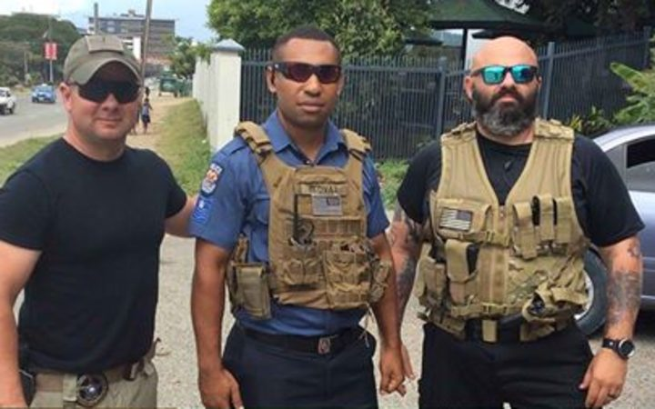 Personnel from US security firm Laurence Aviation & Security Group flank a Papua New Guinea policeman.