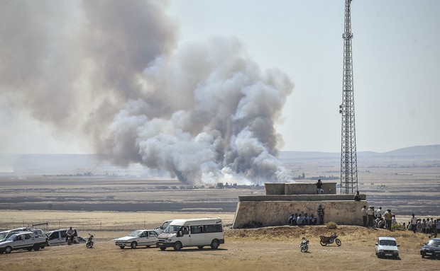 Smoke rises as Islamic State fighters and Kurdish armed groups clash in the Syria-Turkey border town of Kobane on 26 June.