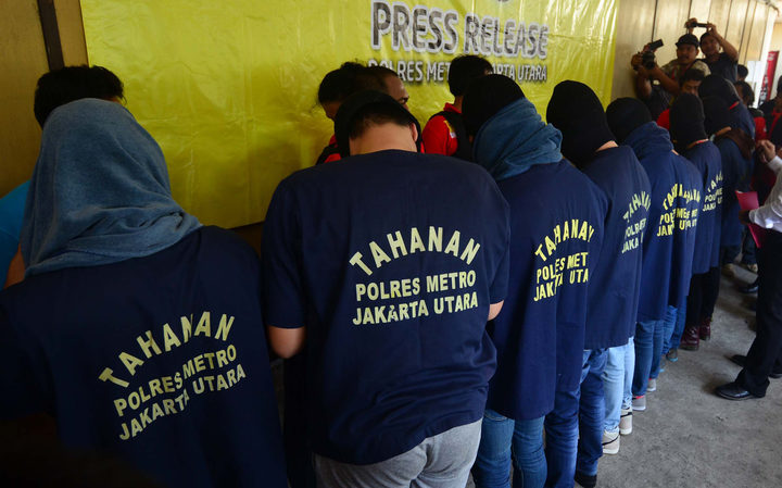 Men arrested in a recent raid stand in line during a news  conference at a police station in Jakarta on 22 May.