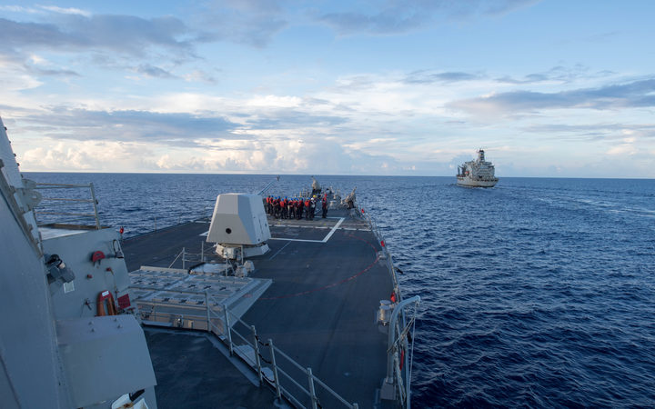 Arleigh Burke-class guided-missile destroyer USS Dewey prepares for a replenishment-at-sea with USNS Pecos, right, in the South China Sea on 19 May 2017.