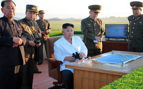 This undated picture released from North Korea's official Korean Central News Agency shows North Korean leader Kim Jong-Un (C) inspecting the test of a new anti-aircraft guided weapon system organized by the Academy of National Defence Science at an undisclosed location.