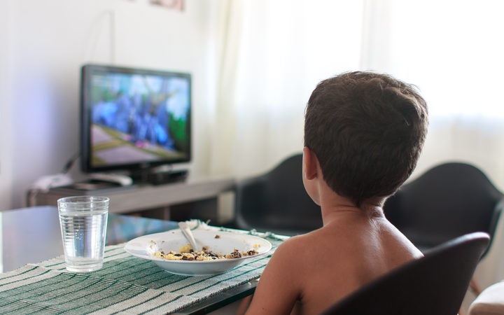 A young boy distracted watching TV while eating lunch