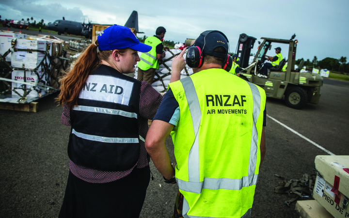 Aid workers and the Royal New Zealand Air Force personnel loading supplies