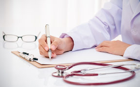 A doctor with a stethoscope writes up a medical record