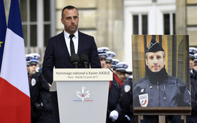 Etienne Cardiles gave a moving address at the ceremony of remembrance for his  partner, policeman Xavier Jugele, whose portrait is placed by his side.