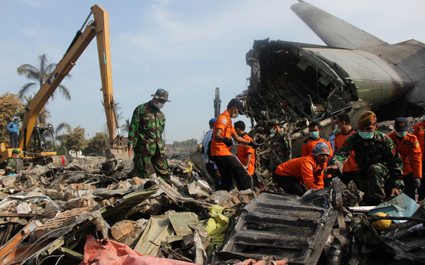 Soldiers search the tail wreckage at the crash site of the aircraft on Wednesday.