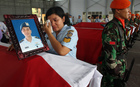 A relative of military personnel grieves during a send-off ceremony at the military airbase in Medan on 1 July.