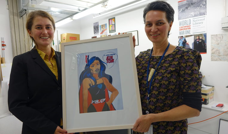 Catherine Bisley, left, and Ariana Tikao, right, both curators at the Turnbull Library, holding a piece of art by Robyn Kahukiwa.