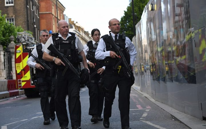 Armed police officers patrol the streets from Borough Market towards The Shard in London.