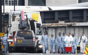 The white van used in the attack on London Bridge is hoisted on top of a flat-bed truck as police work on gathering evidence and securing the area.
