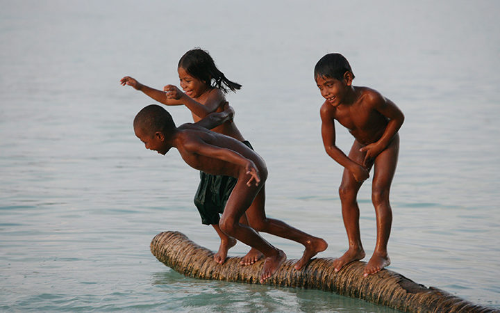 Children in Kiribati play on a partially submerged coconut trunk.