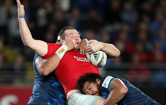 British and Irish Lions captain Ken Owens (C) is tackled by Blues' Alex Hodgman (L) and Steven Luatua (R) during the rugby match between The British and Irish Lions and Auckland Blues at Eden Park.