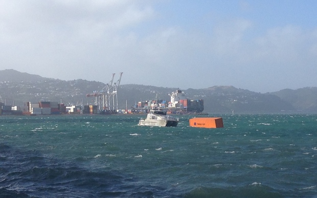A photo shows containers floating in Wellington Harbour.
