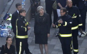 British Prime Minister Theresa May meeets firefighters as she visits the remains of Grenfell Tower.