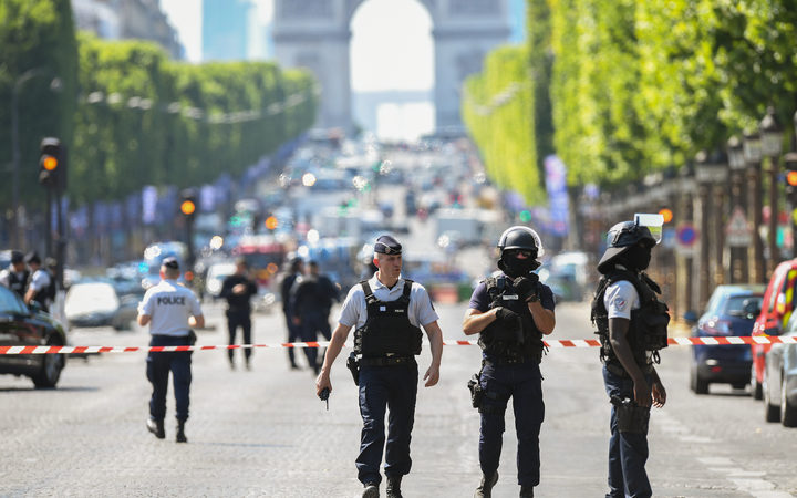Police patrol the Champs-Elysees after a car crashed into a police van before bursting into flames.