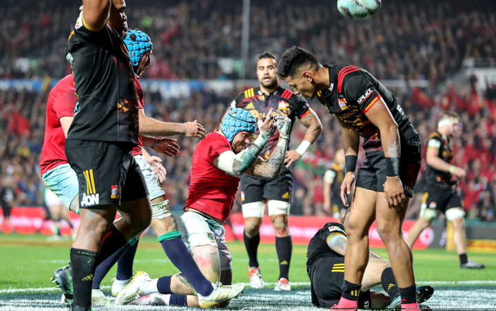 Lions player Jack Nowell celebrates scoring their third try as Chiefs players gather themselves.