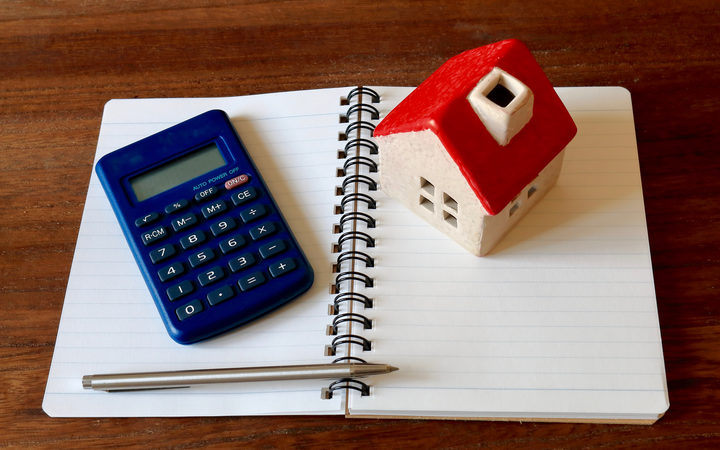 A calculator, a model of a house, a pen and a notebook - to illustrate financial planning and household budgets.