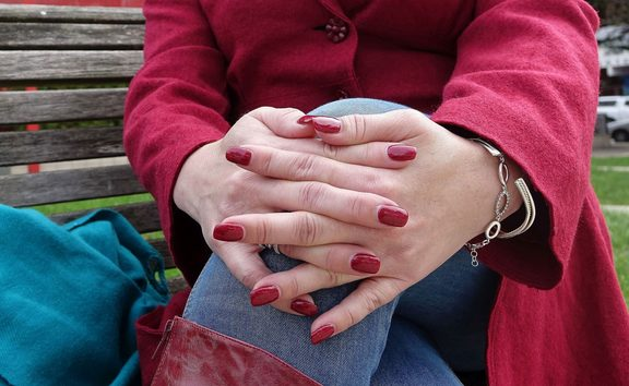 close up of hands as women sits on bench outside