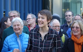 Sarah Thomson, at centre, with supporters outside the High Court in Wellington.