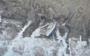 The stricken yacht on the reef where it washed up.
