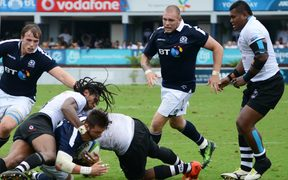 Scotland's Ross Road (3rd L) driving through Fiji's defence for the try line during the one-off test in Suva.