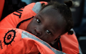 child from African origin looks on as she is rescued from a distressed vessel by a member of Proactiva Open Arms NGO in the mediteranean sea some 20 nautical miles north of Libya on October 3, 2016.