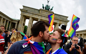 Two men kiss as they attend a rally of gays and lesbians in front of the Brandenburg Gate in Berlin on 30 June, 2017.