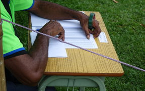 A polling officer reads an electoral roll to call out names for voters to step into the polling booth during the Papua New Guinea 2017 election.