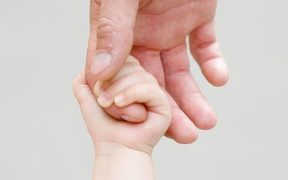 A close up of a child holding and adult's hand